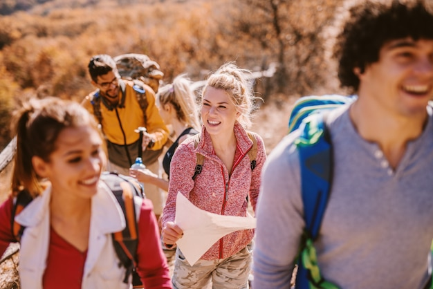 Hikers climbing the hill. selective focus on blonde woman holding the map.