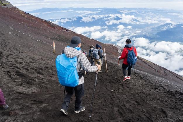 Hikers climbing on yoshida trail on fuji mountain in climbing season