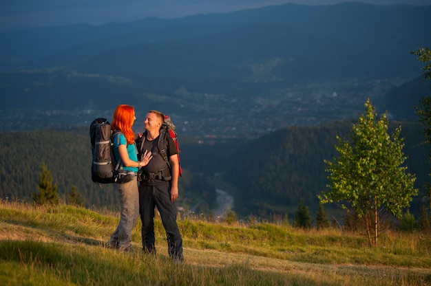 Hikers couple standing on the road in the mountains