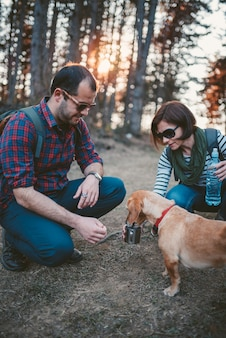 Hikers giving water to her dog in the forest