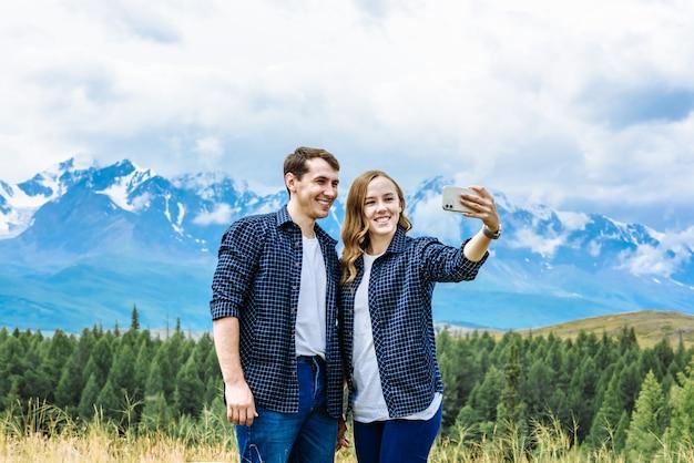 Путешественники в такой же одежде делают селфи в горах