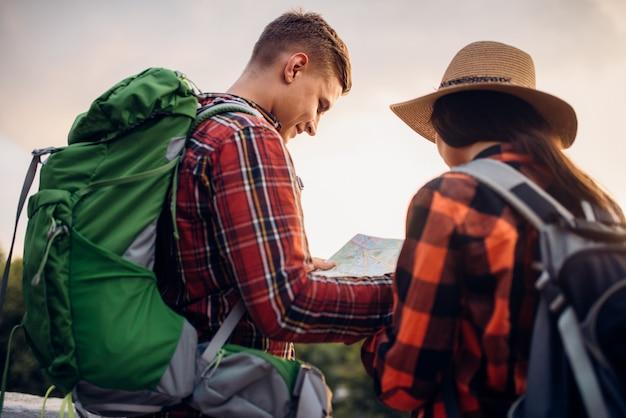 Путешественники смотрят на карту, экскурсия в туристический город