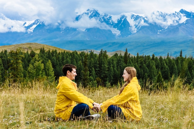 Hikers man and woman sit holding hands against the backdrop of the alpine mountains on their vacation travel.