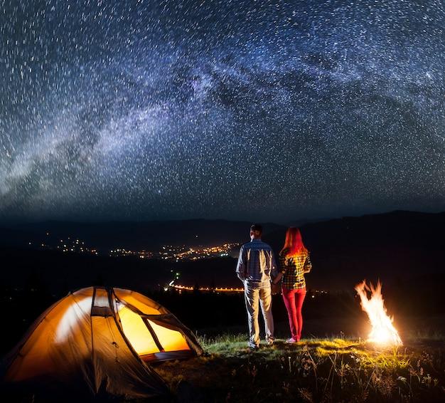 Hikers near bonfire and enjoying starry sky