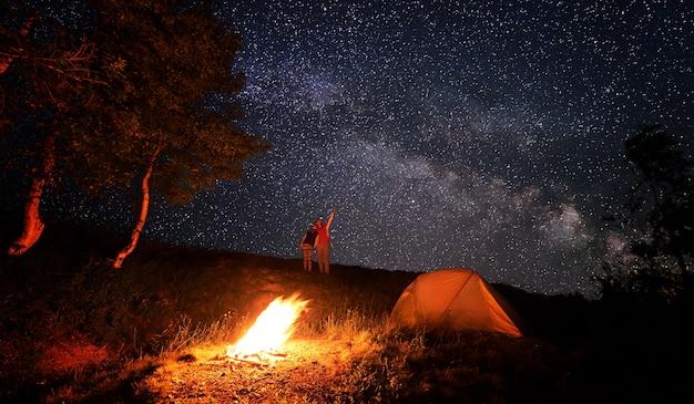 밤 캠핑에서 캠프 파이어와 텐트 근처 등산객