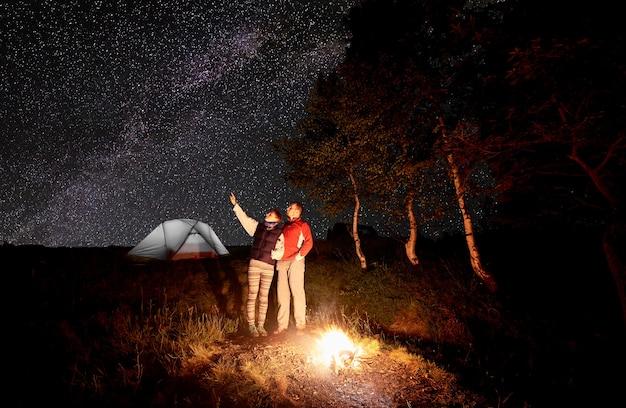 キャンプファイヤーの近くのハイカーと夜のキャンプのテント
