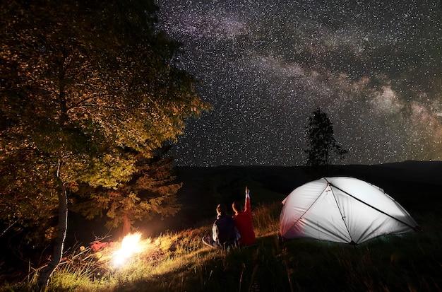 Путешественники возле костра и палатки в ночном кемпинге