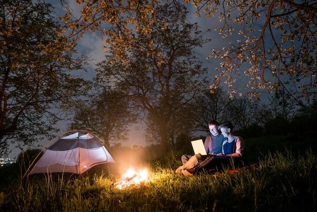 夜のキャンプファイヤーとテントの近くのハイカー