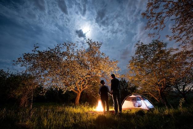 Путешественники возле костра и туристической палатки ночью
