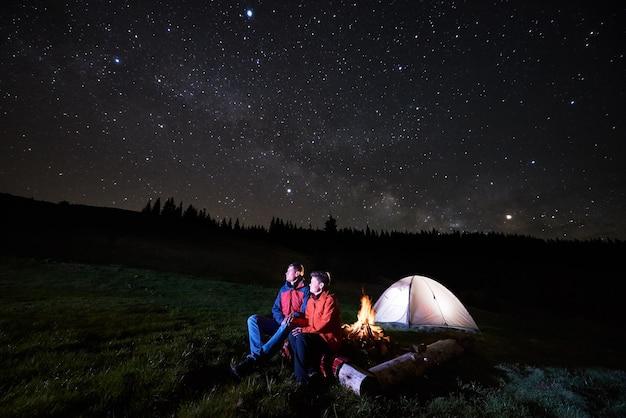 夜のキャンプファイヤーと観光テントの近くのハイカー