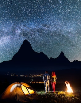 Hikers near campfire and glowing tent at night under stars