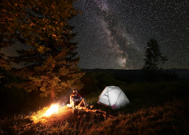 Hikers near campfire and tent at night camping