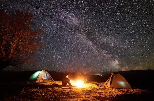 별이 빛나는 하늘 아래 모닥불 근처에서 쉬고 등산객