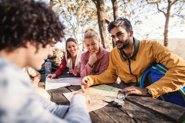 Hikers sitting on the bench at the table in the woods and looking at map