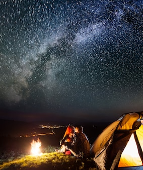 Hikers sitting and kissing near campfire and tent under stars