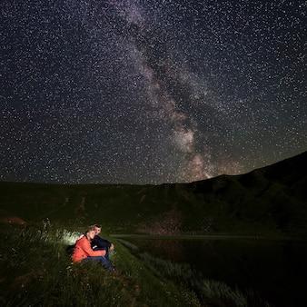 Путешественники, сидя на берегу озера ночью