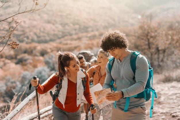空き地の上を歩くハイカー。フォアグラウンドのカップルで地図を見て正しい方向を探しています。秋の時間。