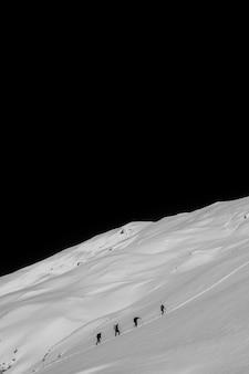 밤에 가파른 눈 덮인 언덕을 걷는 등산객
