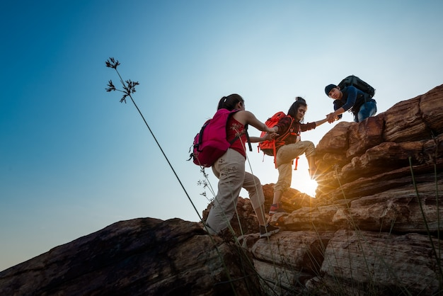 Hikers walking with backpack on a mountain at sunset. traveler going camping. travel concept.