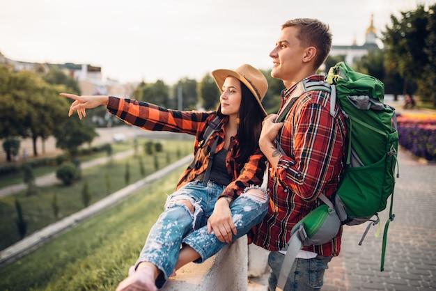 배낭을 짊어진 등산객들은 휴가를 떠나 관광 도시를 관광합니다. 여름 하이킹. 젊은 남녀의 하이킹 모험