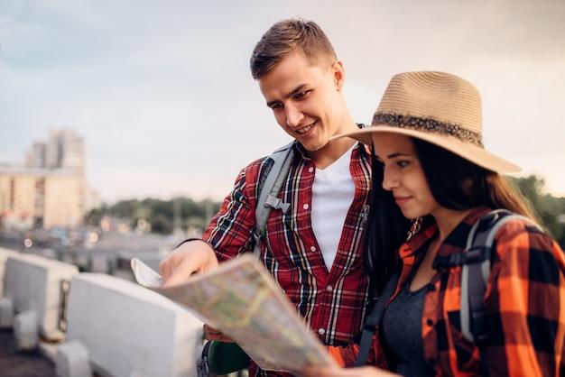 배낭을 든 등산객은지도, 관광 도시 여행을 찾습니다. 여름 하이킹. 젊은 남녀의 하이킹 모험