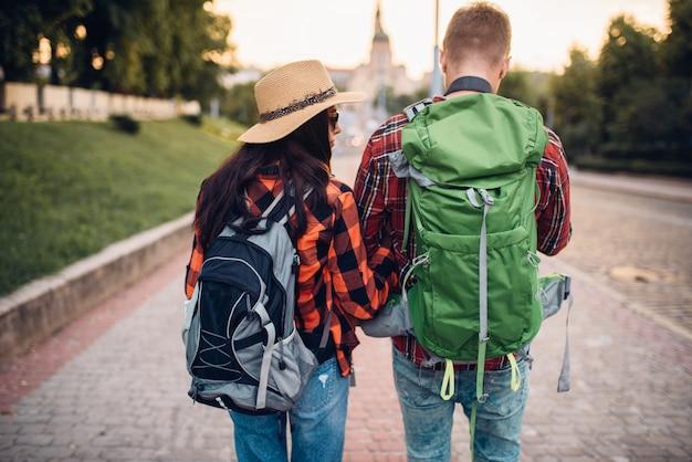 Путешественники с рюкзаками на экскурсии, вид сзади