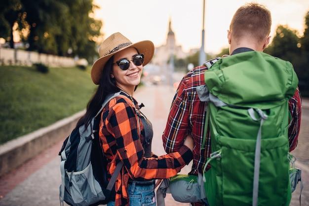 Путешественники с рюкзаками на экскурсии в туристическом городке, вид сзади. летний поход. поход приключение молодого мужчины и женщины