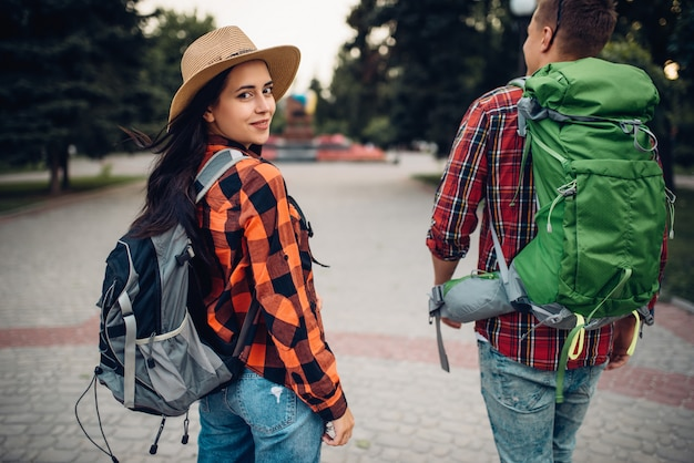 Hikers with backpacks traveling in tourist town