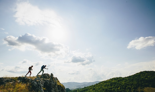 Hikers with backpacks walking on top of a mountain and enjoy hiking