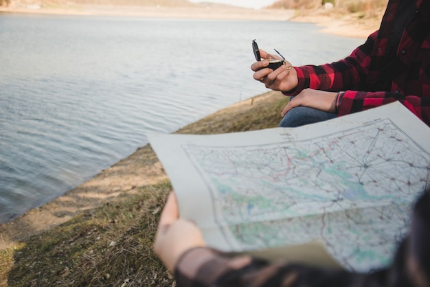Hikers with map and compass by the lake