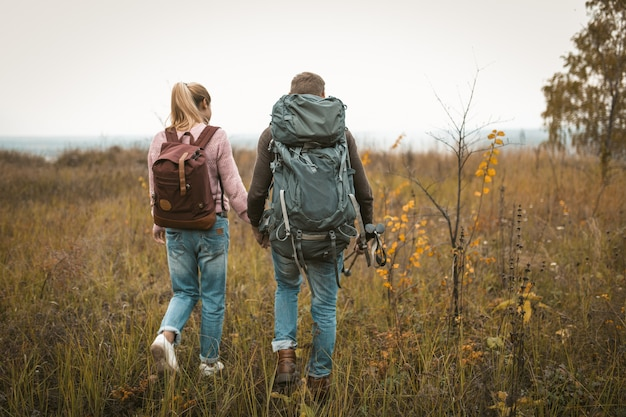 Hiking in autumn nature, couple of backpackers makes their way across the field, rear view of man and woman