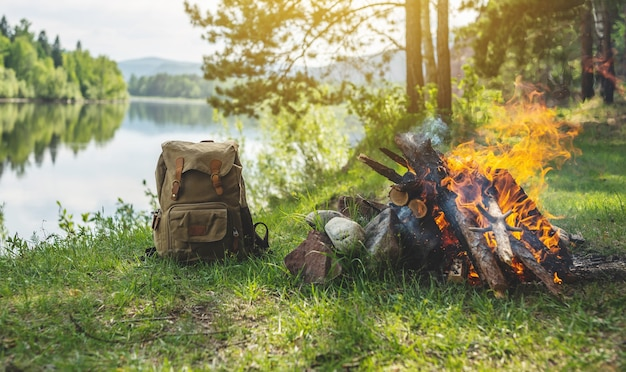 모닥불 옆 강변의 숲에서 하이킹 배낭