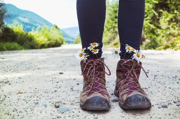 Походные ботинки крупным планом. девушка турист в сапогах с ромашками