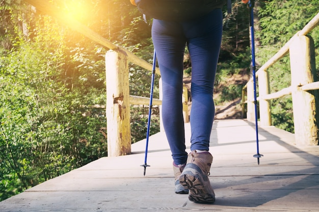 Походные ботинки крупным планом. девушка-турист ступает по деревянной тропе