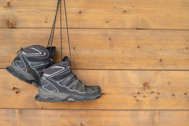 Hiking boots hanging on a wooden wall