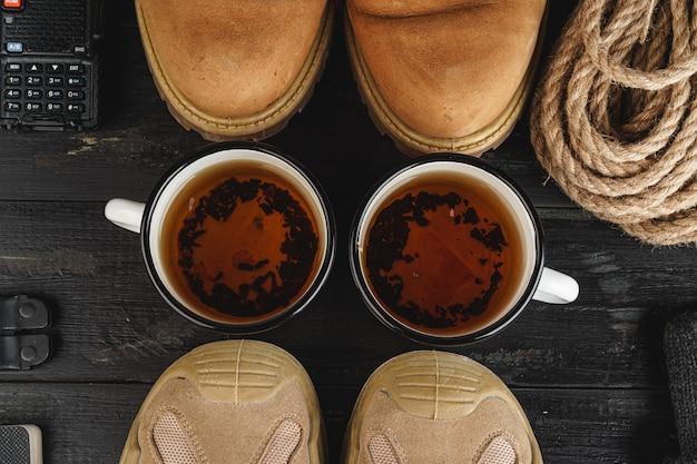 Походные ботинки с оборудованием для походов, чашка чая на деревянной доске