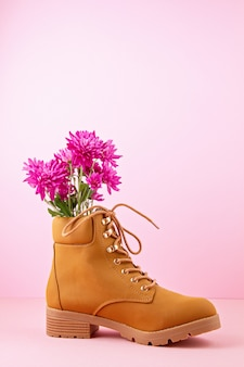 Hiking boots with pink flowers inside over the pink pastel background.