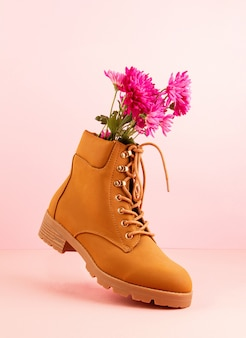 Hiking boots with pink flowers inside over the pink pastel background