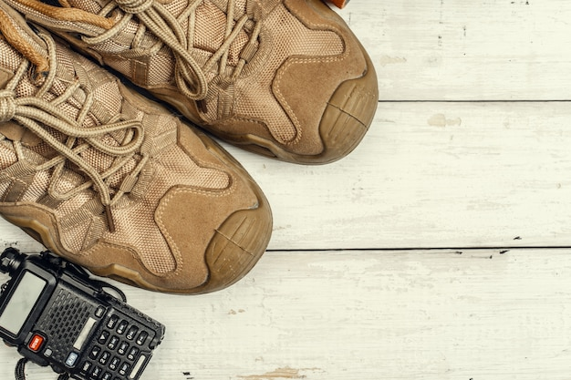 Hiking boots with travel accessories on grunge background