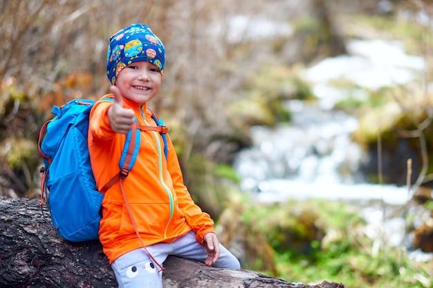 ハイキングの子供の小さな女の子は、バックパックの親指を上にして旅行します。アウトドアスポーツの肖像画のクローズアップ