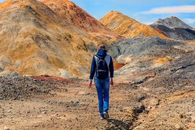 Hiking concept. young woman goes walks among the hills, view from the back. landscape like a planet mars surface. solidified red-brown black earth surface.