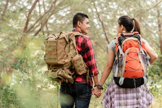 森の中を手をつないで歩いているカップルのアジアのバックパッカーをハイキングします。