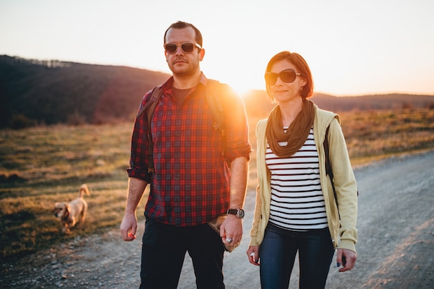 Hiking couple with dog on a dirt road during sunset