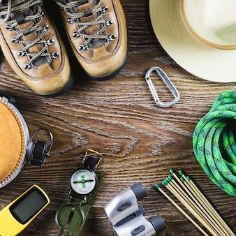 Туризм оборудование с сапоги, компас, бинокль, спички, сумка на деревянных фоне. концепция активного образа жизни.