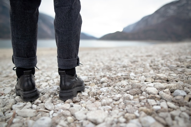 Hiking girl in nature. low angle view of generic sports shoe and legs on pebble dirt road
