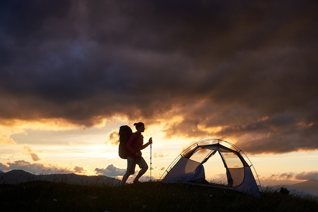 Hiking girl near tent, sunset time in mountains of romania