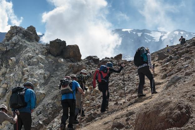 Походная группа людей по туристической тропе поднимается по крутому склону к кратеру действующего вулкана.