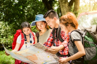 Hiking - hikers looking at map. Couple or friends navigating together smiling happy during camping travel hike outdoors in forest. Young mixed race Asian woman and man.