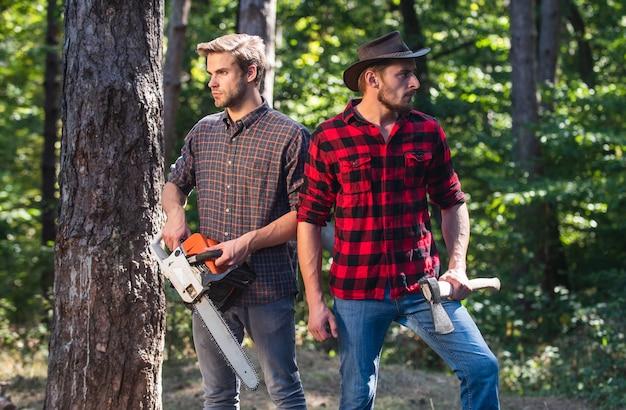深い森でのハイキング。休暇中の森林管理。夏または春の活動。男性農家は森でリラックスします。レンジャーは木こりの道具を使います。チェーンソーと斧で木こり。薪を収穫します。