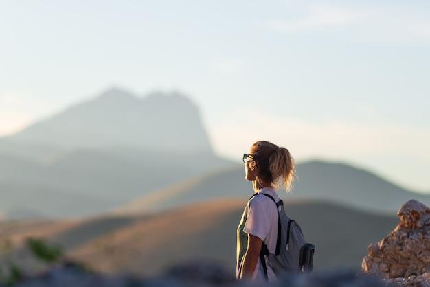 Поход в национальный парк гран-сассо, горы региона абруццо, апеннины, италия. женщина, глядя на пейзаж гор представления. летние мероприятия на свежем воздухе.